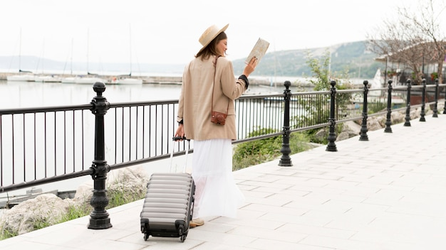 Full shot woman holding baggage