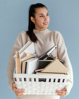 Full shot woman holding basket with books