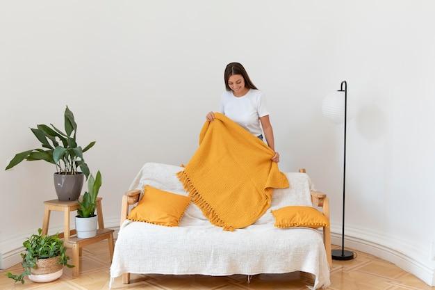Full shot woman holding blanket