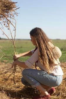 枝を持ったフルショットの女性