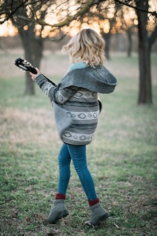 Полный выстрел женщина, держащая гитару