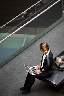 Full shot woman holding laptop
