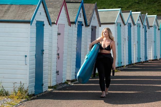 Full shot woman holding paddleboard