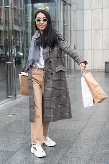 Полный выстрел женщина, держащая хозяйственные сумки