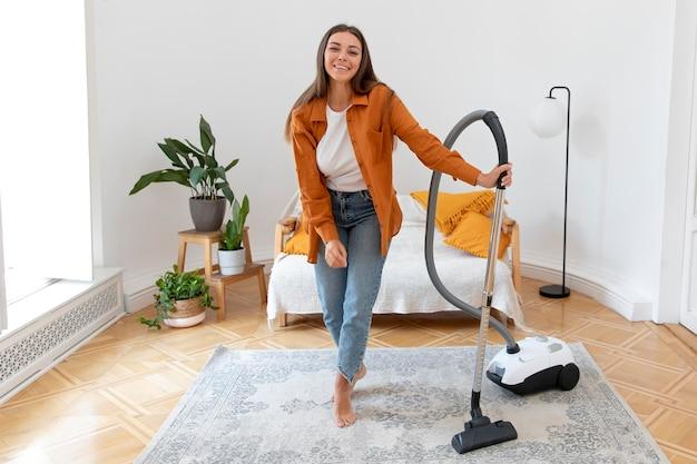 掃除機を持っているフルショットの女性