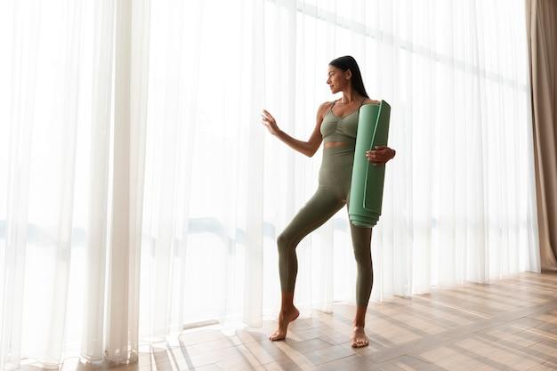 Donna a tutto campo che tiene il tappetino da yoga a casa