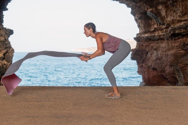 Donna a tutto campo che tiene il tappetino da yoga