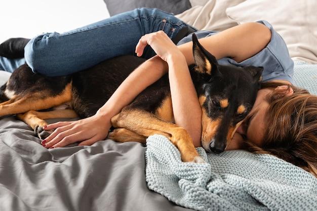 Donna del colpo pieno che abbraccia cane a letto