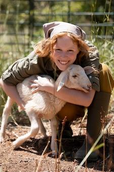 子羊を抱き締めるフルショットの女性