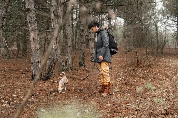 Полный снимок женщины в лесу с милой собакой