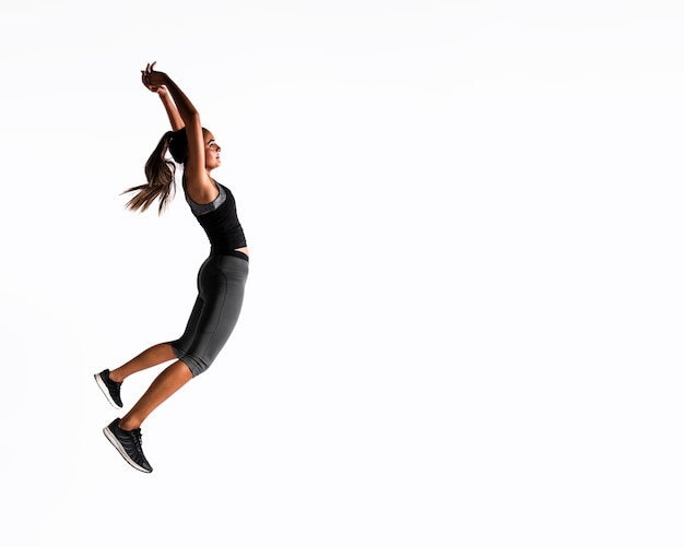 Full shot woman jumping indoors