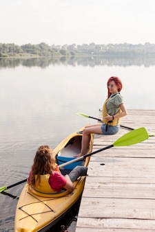 Full shot woman in kayak with friend on dock