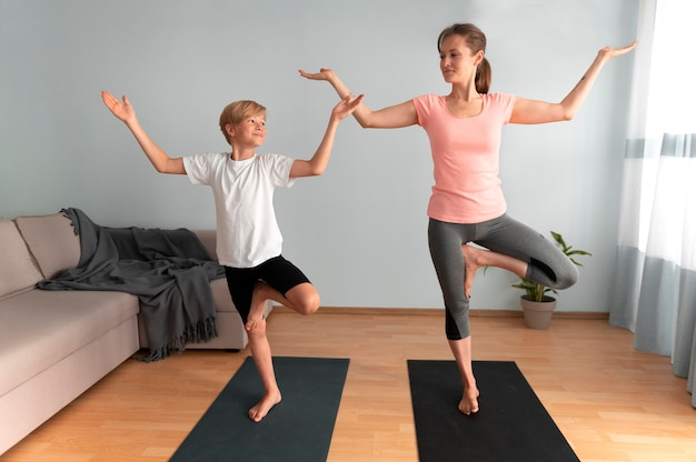 Full shot woman and kid doing yoga