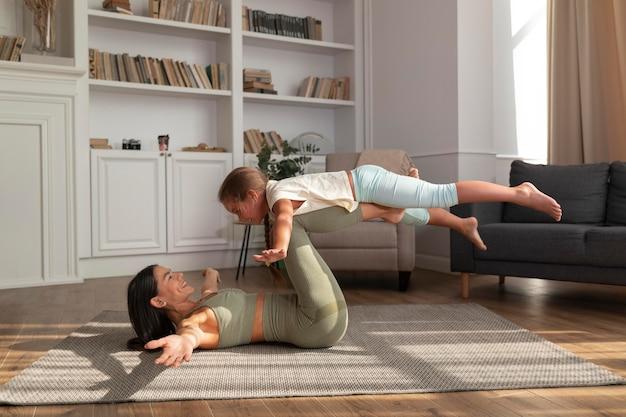 Donna e bambino a tutto campo che fanno yoga