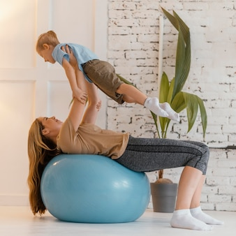 Full shot woman and kid exercising together