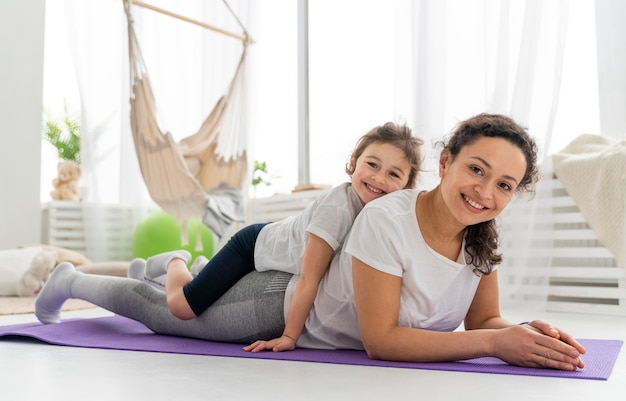 Full shot woman and kid on mat