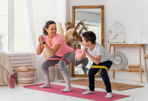 Full shot woman and kid training with resistance band