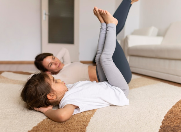 Full shot woman and kid working out on floor