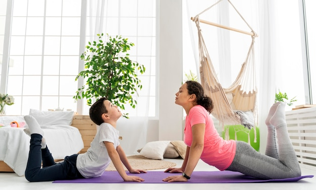 Full shot woman and kid on yoga mat