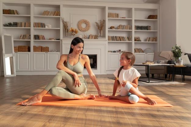 Donna e bambino a tutto campo sul tappetino da yoga