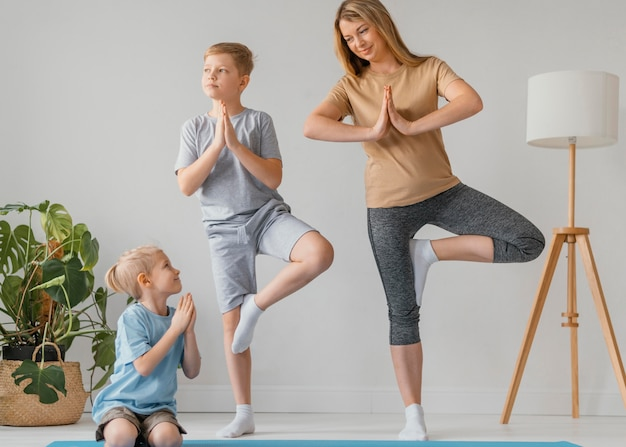 Full shot woman and kids exercising