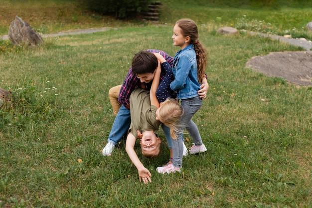 Donna e bambini a tutto campo che giocano