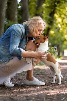 Full shot woman kissing dog