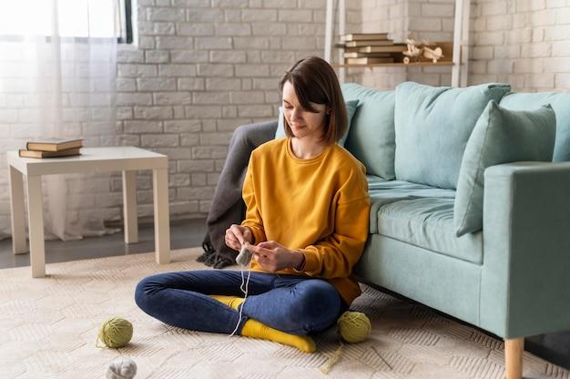 Donna del colpo pieno che lavora a maglia a casa