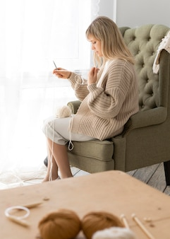 Full shot woman knitting indoors