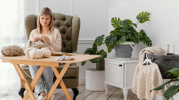 뜨개질을하는 전체 샷된 여자 프리미엄 사진
