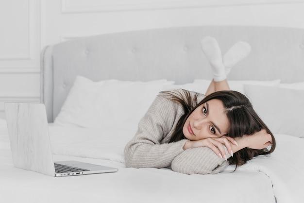Donna piena del colpo che risiede nel letto