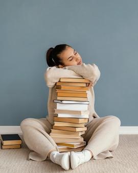 Donna piena del colpo che pone sulla pila di libri