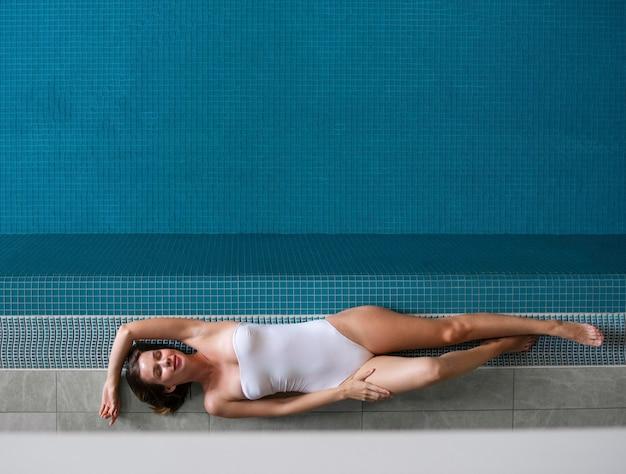 Full shot woman laying near pool