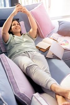ソファに横たわるフルショットの女性
