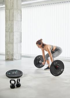 Full shot woman lifting weights