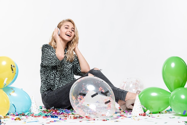 Full-shot woman listening to music surrounded by balloons