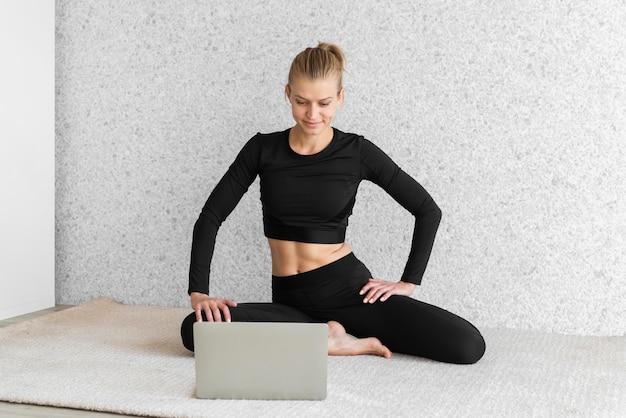 ノートパソコンを見ているフルショットの女性