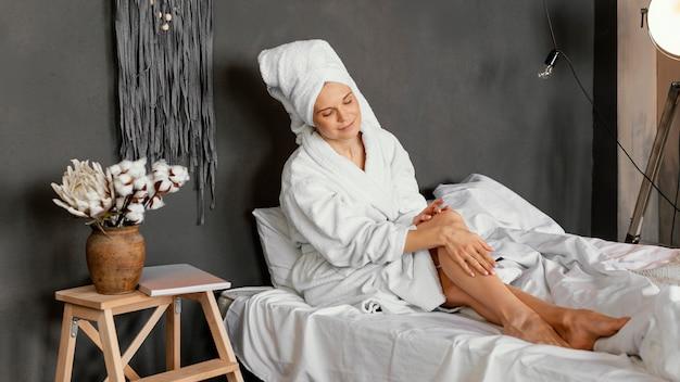 Full shot woman massaging leg