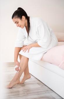 Donna piena del colpo che massaggia le gambe
