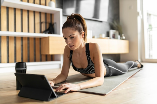 Full shot woman on mat with tablet