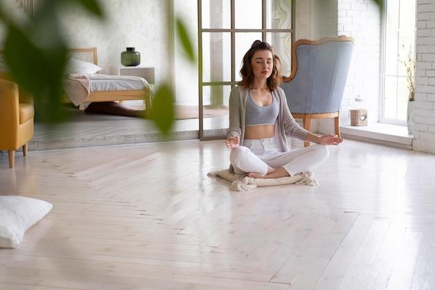 Donna a tutto campo che medita sul pavimento