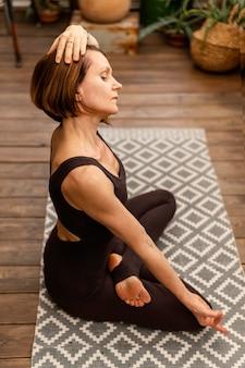屋内で瞑想するフルショットの女性
