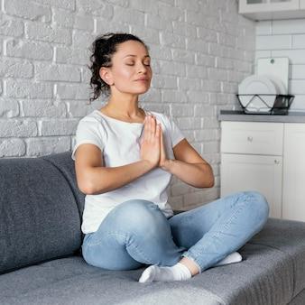 ソファで瞑想するフルショットの女性