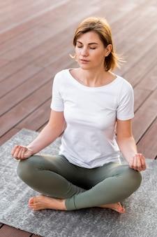 Полный выстрел женщина медитирует на коврике на открытом воздухе