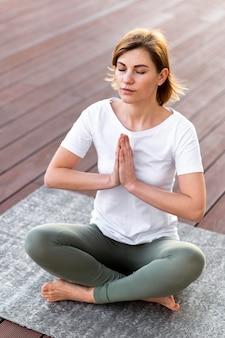 Полный выстрел женщина медитирует на коврике