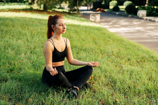 Full shot woman meditating outdoors
