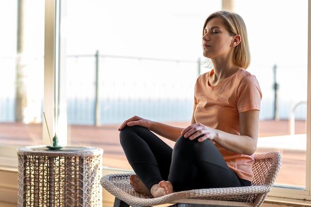 Женщина в полный рост на стуле, медитируя