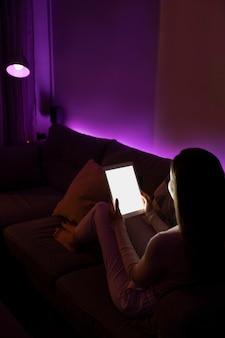 Женщина в полный рост на диване с планшетом