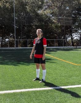 Женщина в полный рост на футбольном поле