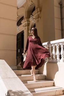 Полный снимок женщины на лестнице на открытом воздухе